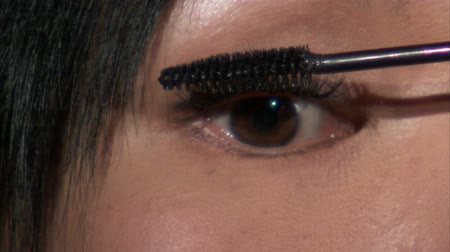 olho : A close up shot of an Asian woman putting mascara on one eye on black.