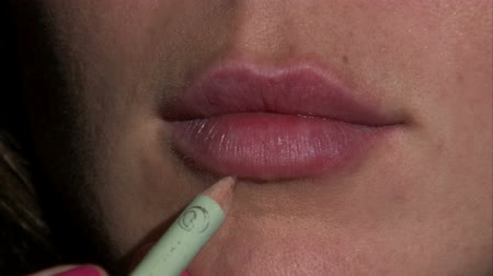 határozza meg : A close up of a womans lips. Lip liner is then applied to the outside of the lips. Stock mozgókép