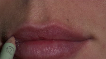 határozza meg : An extreme close up of a womans lips. Lip liner is then applied to the outside of the lips. Stock mozgókép