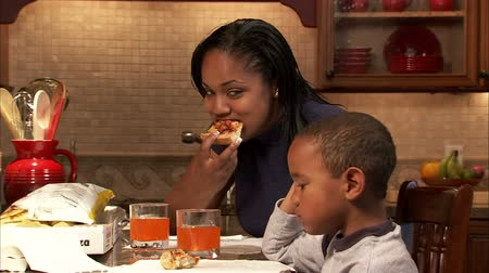 africký : A dolly shot of a boy and his mother eating pizza.