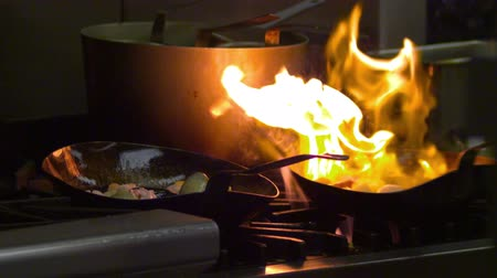 cooking pots : Close up slow motion of a chef cooking over an open flame in a nice restaurant in Salt Lake City, UT Stock Footage