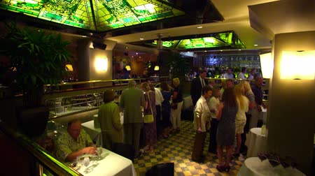 ławka : People gather at a restuarant in Salt Lake City. Some stand in line for a buffet, while others socialize.