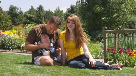 apu : A young couple with their new baby in a beautiful garden.