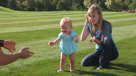 uczenie się : Slow motion shot of a young couple with their baby girl playing in a garden. Wideo