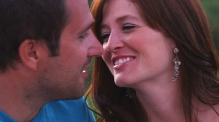 miłość : A close-up slow motion shot of a young couple talking and kissing in a beautiful garden.