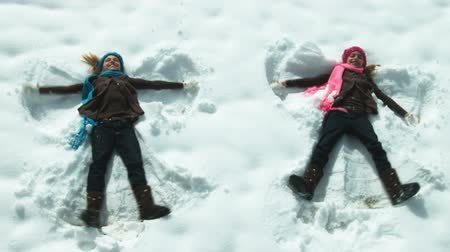 queda de neve : Twin girls make angels in the snow