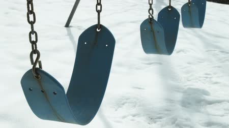 plac zabaw : Empty blue swings shift in the breeze, contrasted against the snow on the ground. Wideo