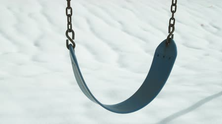 żelazko : An empty blue swing shift in the breeze, contrasted against the snow on the ground.