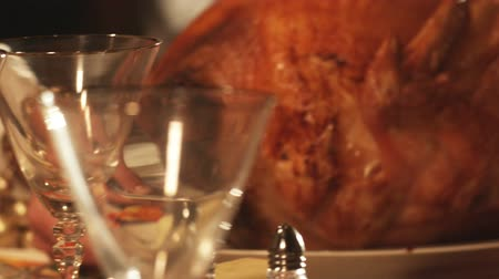 hacı : Close-up pan of decorations on a Thanksgiving table as the roasted turkey is placed on it. Stok Video