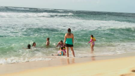 havaiano : Mother overlooks as children play in waves on a sunny beach in Hawaii