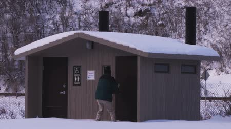 запертый : Man desperately and fruitlessly tries to open restroom doors of a public outhouse at a snowy road stop. He runs behind the outhouse, evidently intending to urinate there.