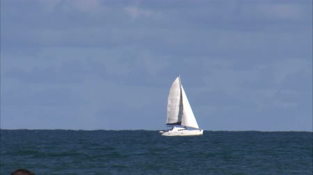 esquerda : A shot of a sailboat sailing from the left of the screen to the right. Towards the end of the clip, a parasailing boat passes by.