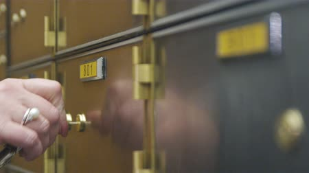 odemknout : Close up of hand and key opening a safety deposit box