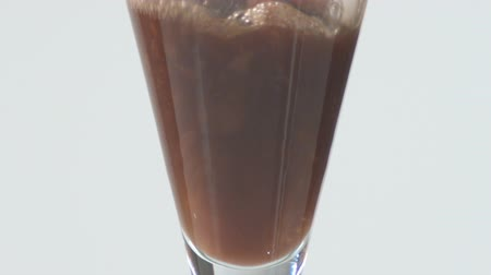 unfilled : Close-up shot at a high angle of an empty and clear glass container filling with a brown liquid backdropped with white. Stock Footage
