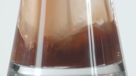 unfilled : Close-up footage of the base of a clear glass cup being filled by a brown liquid. Interesting lighting effects on glass.