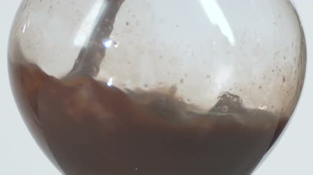 zaoblený : Slow motion close-up footage of a rounded wine glass filling with a brown liquid. Interesting shot of liquid curling from the sides of the glass.