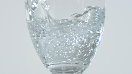 zaoblený : Close up of a stemmed glass being filled with pouring water. White background.