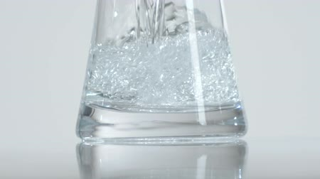 zaoblený : Close up of a glass container being filled with water. White background. Dostupné videozáznamy