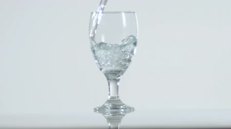 üdítő : Slow motion footage of a clear liquid filling an empty stemmed glass. Stock mozgókép