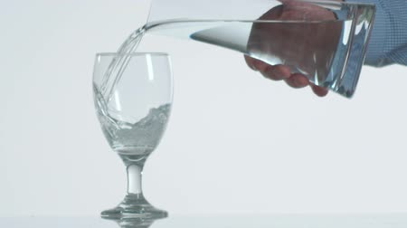 zaoblený : Slow motion close up of a hand filling an empty wine glass with water from a decanter.
