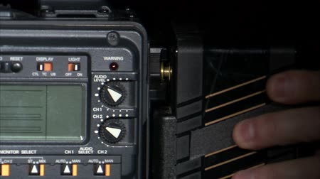 pil : A close up shot of a battery being attached to the back of a camera