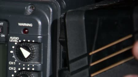 pil : A close up shot of a battery being attached to the side of a camera