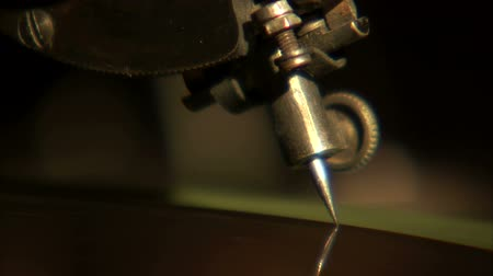 kapatmak : An extreme close up of an old needle dropping on top of a record.