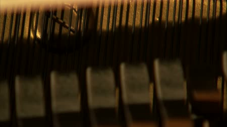 пианино : A shot of piano hammers striking the strings of a piano. The strings are in the foreground as the hammers are out of focus.