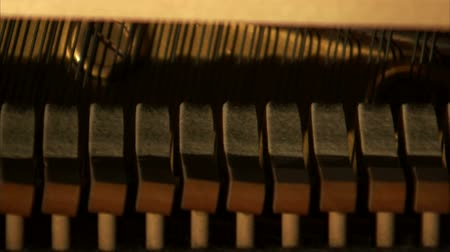 пианино : A medium shot of piano hammers striking the strings of a piano.