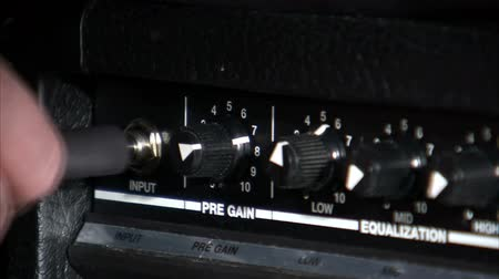 kytara : A medium shot of the knobs on a guitar amp. A guitar cord is then placed into the amp.