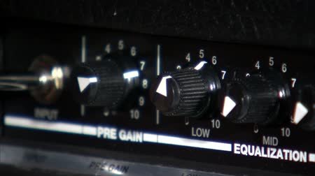 amplificador : A close up of the knobs on a guitar amp. A guitar cord is then placed into the amp, and the camera rack focuses on the cord.