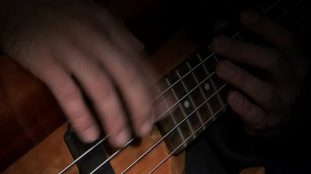 kytara : A wide shot of hands playing a bass guitar . There is a black background. Dostupné videozáznamy