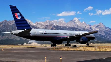 идущий : Shot of airplane leaving airport runway. Mountains are seen in the background.