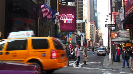 quadretti : Colpo di un incrocio nei pressi di Times Square a New York City che mostra auto di passaggio e la M e il mondo di M in background.