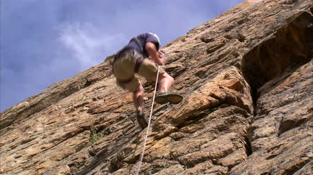alpinista : Shot of a mountain climber climbing up the face of the mountain Stock Footage