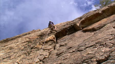 wspinaczka górska : Shot of a mountain climber climbing up the face of the mountain Wideo