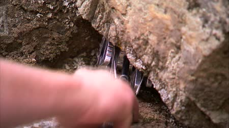cordas : Shot of a mountain climbers hand placing a spring loaded camming device in a crack in the rocks.