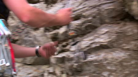 alpinista : Shot of a mountain climber taking a camming device off of his harness and placing it in a crack in the rocks. Stock Footage