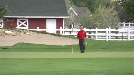 яма : A medium shot of a golfer on the green. He removes the flag and gets ready to putt.