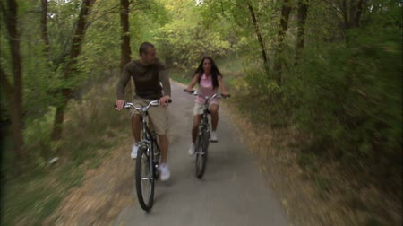 дата : A front moving shot of a couple riding their bikes through a tree covered bike path.