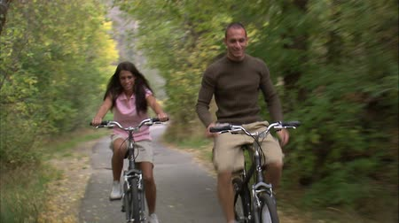 tarihleri : A front moving shot of a couple riding their bikes through a tree covered bike path. The man rides with no hands.