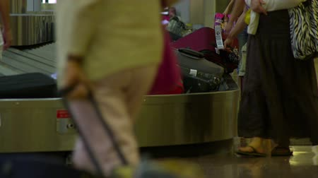 reclaim : A man takes his bag of the conveyor as others wait to see their luggage at baggage claim. Stock Footage