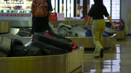 reclaim : People walk through the baggage claim areas as luggage travels around the conveyor belts.