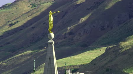 trąbka : The golden-colored statue of Angel Moroni points eastward on top of the LDS Salt Lake Temple. The green and brown mountains can be seen in the background. Wideo