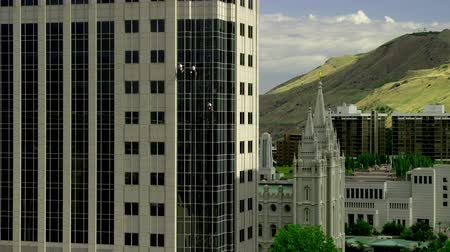 cleaner : Wide shot of men rappelling and washing windows of a building next to the Church of Jesus Christ of Latter-Day Saints Temple in downtown Salt Lake City, UT Stock Footage