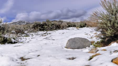 derretido : Time-lapse of melting snow on Utah valley. Some rocks and grass are seen in the video.