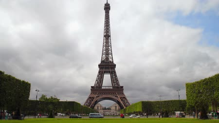 repousante : Time-lapse of Eiffel tower in all its splendor, as it rises above adjoining park and landscaped trees while clouds waft by in background and people and cars pass by below near street in front. Stock Footage