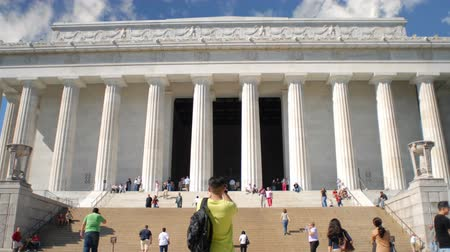 запомнить : Time-lapse of low angle shot of Lincoln Memorial in Washington D.C., with its tall, regal, Greek style architecture including white marble columns, with tourists and many people coming and going and observing below on front steps. Стоковые видеозаписи