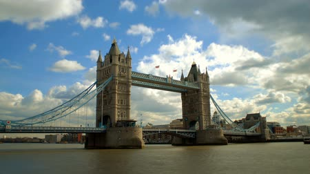 londyn : Full view of famous, historic Tower Bridge in London, England, showing most of bridges adjoining, as well as the River Thames water below, buildings on opposite side of Canal, all under swift fluffy clouds moving along sky above in time lapse.
