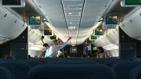 sorok : Medium shot of interior of airplane showing rows of blue seats and white luggage compartments next to individual tv screens with people at front of plane making preparations for flight.